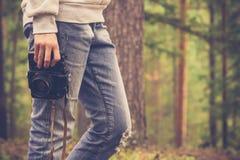 Mujer joven que camina con la cámara retra de la foto al aire libre Imágenes de archivo libres de regalías