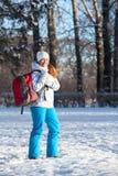 Mujer joven que camina con la mochila en parque del invierno Foto de archivo libre de regalías