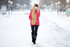 Mujer joven que camina con smartphone al aire libre en invierno Imagen de archivo libre de regalías