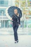 Mujer joven que camina con un paraguas abierto Imagen de archivo