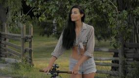 Mujer joven que camina con una bicicleta al aire libre almacen de video