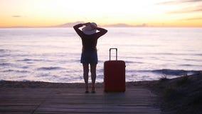 Mujer joven que camina con una maleta en la playa almacen de video