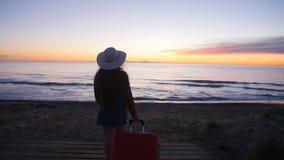 Mujer joven que camina con una maleta en la playa almacen de metraje de vídeo