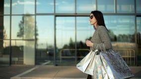 Mujer joven que camina contra una alameda de compras almacen de video