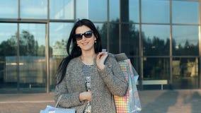 Mujer joven que camina contra una alameda de compras almacen de metraje de vídeo