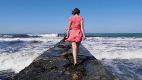 Mujer joven que camina descalzo en el embarcadero del mar mientras que ondas del mar que golpean contra el embarcadero Siga detrá almacen de metraje de vídeo