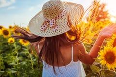 Mujer joven que camina en campo floreciente del girasol, saltando y divirtiéndose Vacaciones de verano fotos de archivo libres de regalías