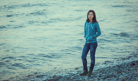 Mujer joven que camina en costa cerca del mar Fotos de archivo