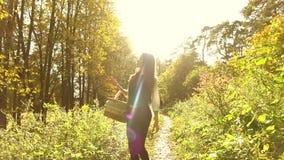 Mujer joven que camina en el bosque del otoño que sostiene una cesta de la comida campestre Clip del steadicam de la cámara lenta almacen de metraje de vídeo