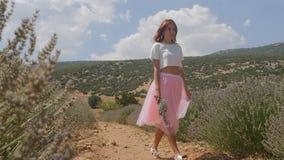 Mujer joven que camina en el campo de la lavanda metrajes