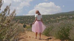 Mujer joven que camina en el campo de la lavanda almacen de metraje de vídeo