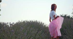 Mujer joven que camina en el campo del lavanda almacen de video