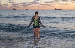 Mujer joven que camina en el océano Imagen de archivo libre de regalías