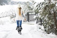 Mujer joven que camina en el parque cubierto con nieve Foto de archivo