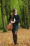 Mujer joven que camina en el parque en un día del otoño Fotografía de archivo