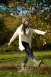 Mujer joven que camina en el parque y que golpea un charco con el pie del agua Foto de archivo