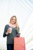Mujer joven que camina en la alameda de compras que hace una llamada con smartpho Fotografía de archivo