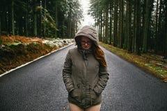 Mujer joven que camina en la carretera de asfalto en bosque imagen de archivo libre de regalías