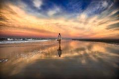 Mujer joven que camina en la playa cerca del océano y que se va en la puesta del sol Imagen de archivo libre de regalías