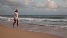 Mujer joven que camina en la playa en la puesta del sol almacen de video