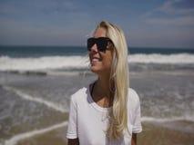 Mujer joven que camina en la playa que mira la cámara y la sonrisa metrajes