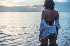 Mujer joven que camina en la playa que se coloca en agua Imagen de archivo libre de regalías