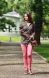 Mujer joven que camina en un parque con un teléfono móvil Fotos de archivo libres de regalías