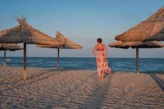 Mujer joven que camina a lo largo de una playa arenosa Imágenes de archivo libres de regalías