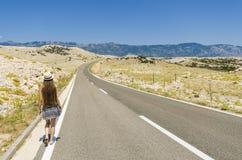 Mujer joven que camina a lo largo del camino vacío Imágenes de archivo libres de regalías