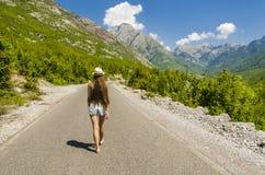 Mujer joven que camina a lo largo del camino vacío Fotos de archivo libres de regalías