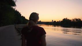 Mujer joven que camina por el río en la puesta del sol almacen de metraje de vídeo