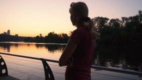 Mujer joven que camina por el río en la puesta del sol en la cámara lenta metrajes