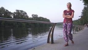 Mujer joven que camina por el río en la puesta del sol en la cámara lenta almacen de video