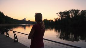 Mujer joven que camina por el río en la puesta del sol en la cámara lenta almacen de metraje de vídeo