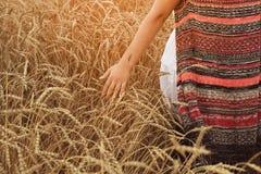 Mujer joven que camina a través de campo y de trigo de los tactos foto de archivo