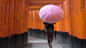 Mujer joven que camina a través de las puertas de Torii con el paraguas