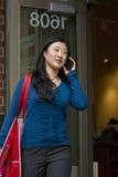 Mujer joven que camina y que habla en el teléfono Fotografía de archivo