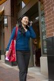 Mujer joven que camina y que habla en el teléfono Imagen de archivo libre de regalías