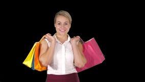 Mujer joven que camina y sostener bolsos de compras mientras que hace un ciertas compras, Alpha Channel almacen de metraje de vídeo