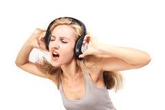 Mujer joven que canta con los auriculares Foto de archivo libre de regalías