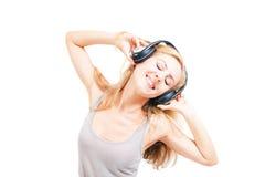 Mujer joven que canta con los auriculares Imágenes de archivo libres de regalías