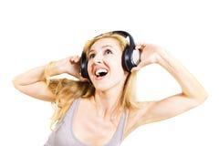Mujer joven que canta con los auriculares aislados Foto de archivo