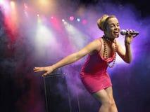 Mujer joven que canta en el micrófono Imagenes de archivo