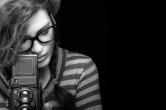 Mujer joven que captura la foto usando cámara del vintage Por monocromático Fotografía de archivo