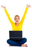 Mujer joven que celebra éxito en la computadora portátil Imagenes de archivo