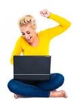 Mujer joven que celebra éxito en la computadora portátil Foto de archivo