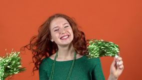 Mujer joven que celebra día del ` s de St Patrick en el baile anaranjado de la pared con los poms del pom metrajes