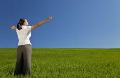 Mujer joven que celebra en un campo verde Fotos de archivo libres de regalías