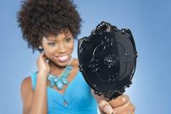 Mujer joven que celebra la mirada del espejo sobre fondo coloreado Imagen de archivo