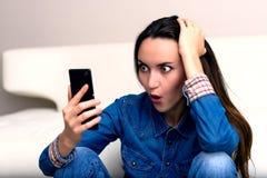 Mujer joven que celebra su cabeza y miradas al smartphone El sentarse en el piso en choque Foto de archivo